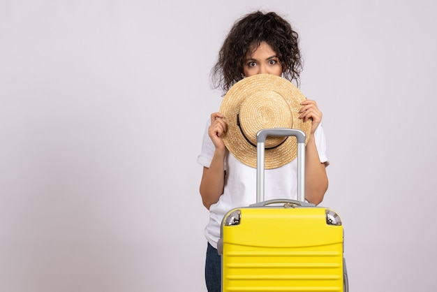 Vista frontale giovane donna con borsa gialla che si prepara per il viaggio su sfondo bianco vacanza turistica volo aereo viaggio colore