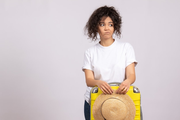 Front view young female with yellow bag preparing for trip on a white background tourist vacation plane voyage color rest flight