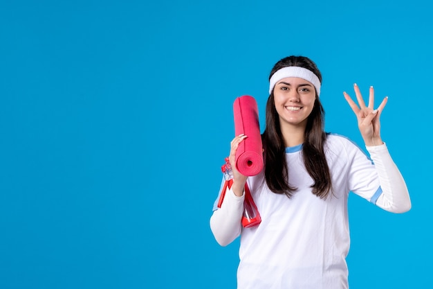 Front view young female with yoga mat on blue wall