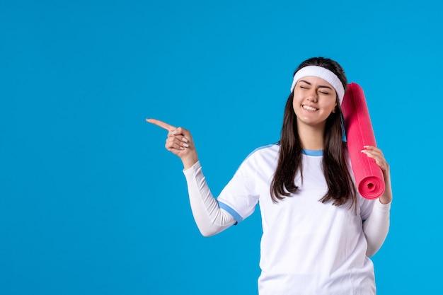 Вид спереди молодая женщина с ковриком для йоги на синей стене