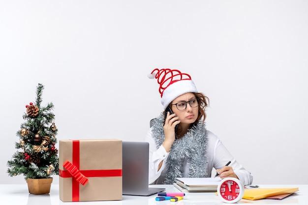Giovane donna di vista frontale al lavoro durante i giorni di festa parlando al telefono su priorità bassa bianca