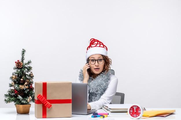 Vista frontale giovane donna al lavoro durante i giorni di vacanza utilizzando laptop parlando al telefono su sfondo bianco