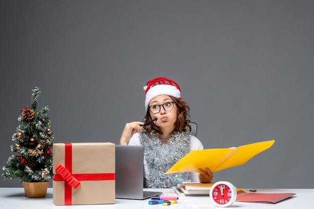 Вид спереди молодая работница сидит перед своим местом и работает с документами на сером фоне