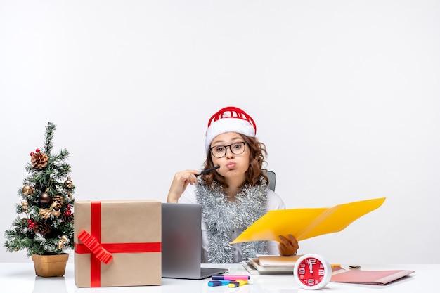 Вид спереди молодая работница сидит перед своим местом и работает с документами на белом столе