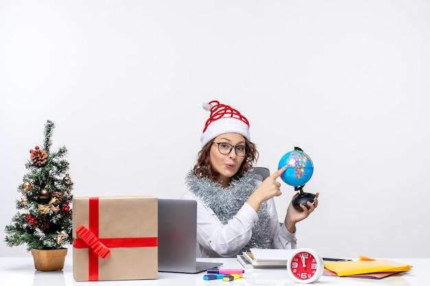 Вид спереди молодая работница, сидящая перед своим местом, держа земной шар на белом фоне