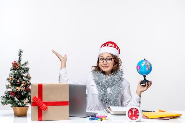 Вид спереди молодая работница, сидящая перед своим местом, держащая земной глобус на белом столе