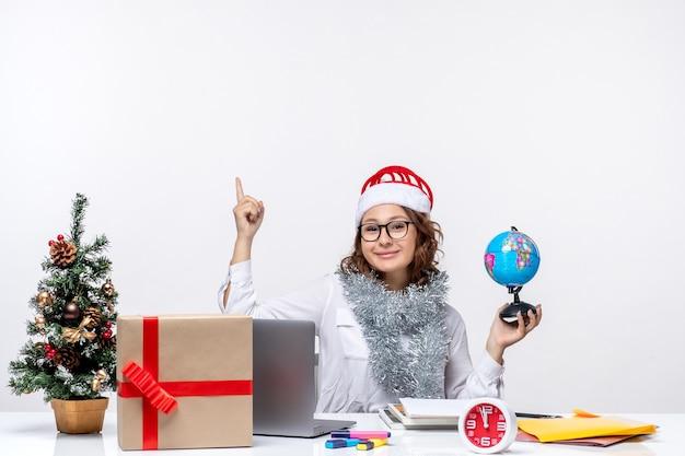 Vista frontale della giovane lavoratrice seduta prima del suo posto tenendo il globo terrestre su sfondo bianco