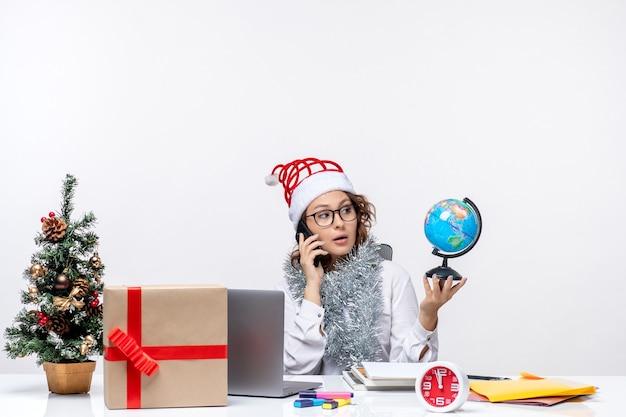 Вид спереди молодая работница сидит перед своим местом, разговаривает по телефону, держа глобус на белом фоне
