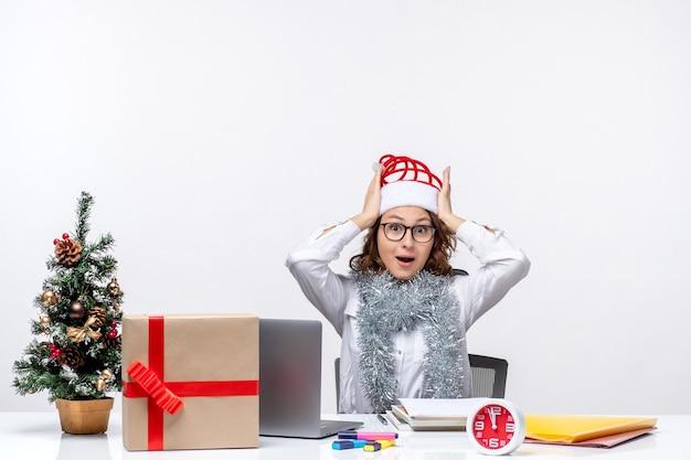 Вид спереди молодая работница, сидящая перед своим рабочим местом на белом полу, женщина, бизнес, стол, офисная работа, работа, рождество