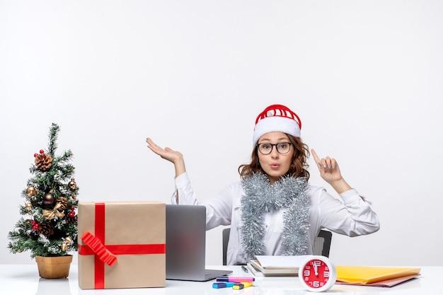 Vista frontale giovane lavoratrice seduta prima del suo posto di lavoro su sfondo bianco