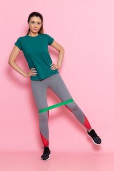 Вид спереди молодая женщина, тренирующаяся на светло-розовой стене, красота, спорт, упражнения, спортсмен, тренировки, стройная