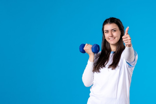 Front view young female working out with blue dumbbells on blue wall