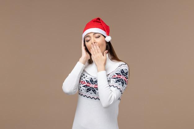 Giovane femmina di vista frontale che sbadiglia nel berretto rosso su sfondo marrone emozione natale capodanno
