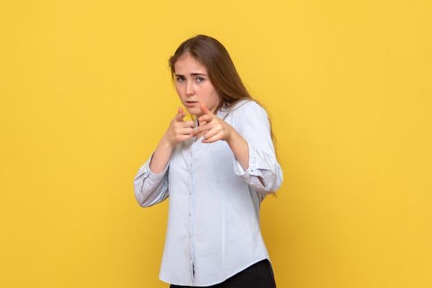 Vista frontale della giovane donna su sfondo giallo bellezza modello colore donna emozione
