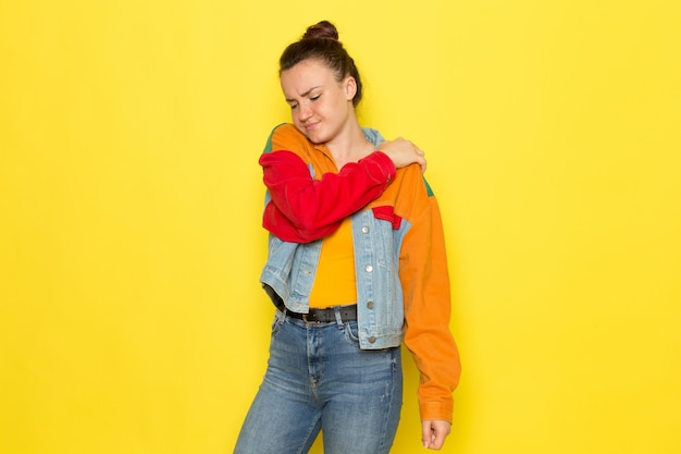 A front view young female in yellow shirt colorful jacket and blue jeans having a back ache
