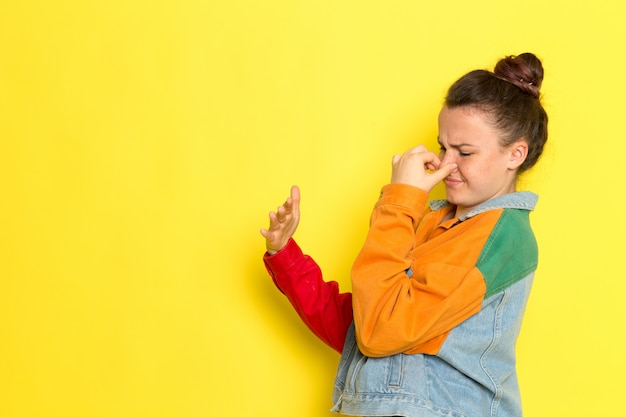A front view young female in yellow shirt colorful jacket and blue jeans holding her nose due to the stinking smell