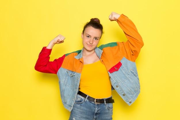 Una giovane donna vista frontale in giacca colorata camicia gialla e blue jeans in posa e flessione