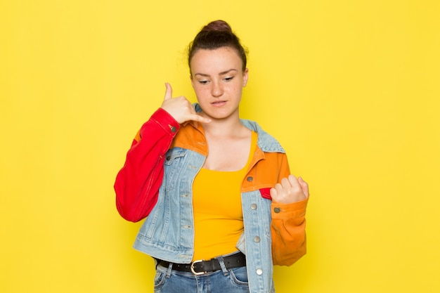 A front view young female in yellow shirt colorful jacket and blue jeans posing