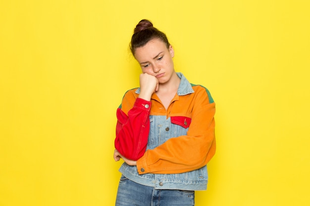 A front view young female in yellow shirt colorful jacket and blue jeans with thinking expression