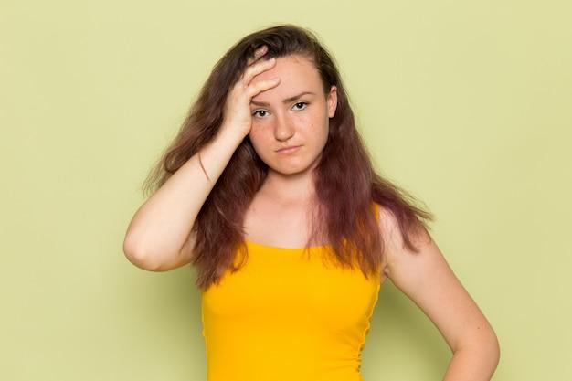 Una giovane femmina di vista frontale in camicia gialla con il mal di testa depresso di emozione della ragazza di espressione