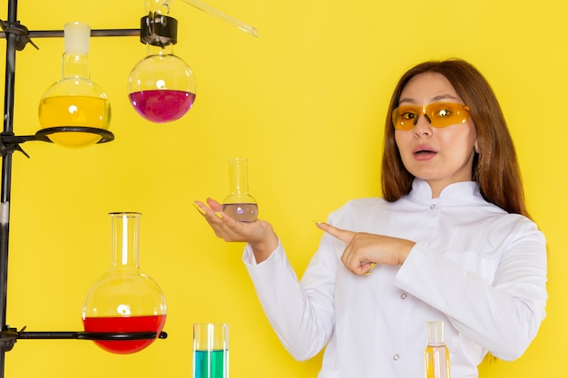 Front view of young feman chemist in white suit in front of table working with solutions