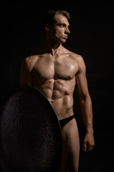 Front view of young fit strong warrior with perfect muscular body. tensed athlete in underwear looking away, posing and holding shield on black  wall. cocept of warrior, strength.