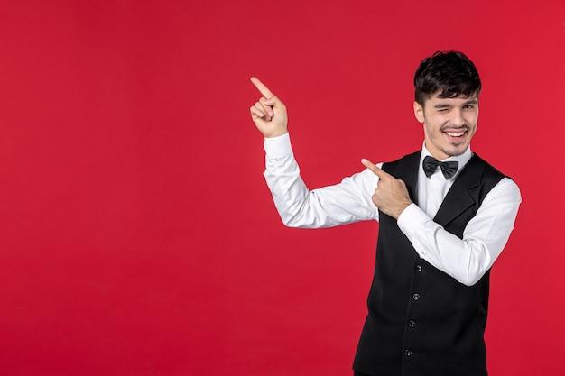 Vista frontale di un giovane cameriere maschio divertente in uniforme con papillon sul collo e rivolto verso l'alto sul lato destro sulla parete rossa