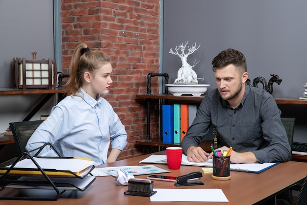 Vista frontale del giovane divertente team dell'ufficio confuso su un problema nell'ambiente dell'ufficio