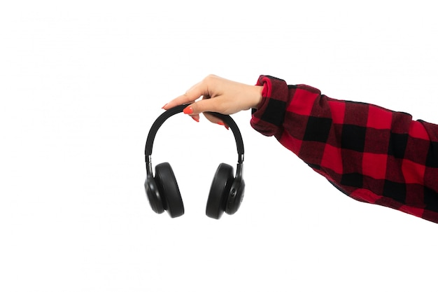 A front view young girl female hand holding black earphones on the white