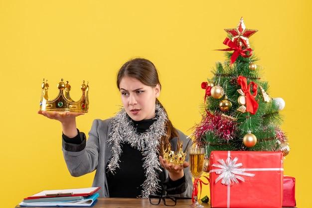 Вид спереди молодая девушка держит большую и маленькую корону и проверяет большую рождественскую елку и подарочный коктейль