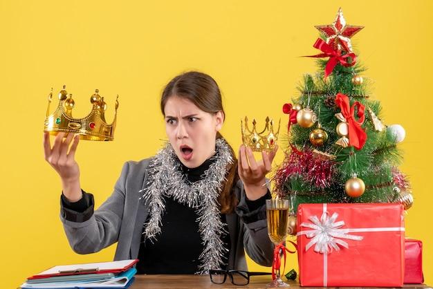 Вид спереди молодая девушка, держащая большую и маленькую корону в руке, рождественское дерево и подарочный коктейль