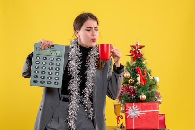 Calcolatrice della holding della ragazza di vista frontale e una tazza di caffè vicino all'albero di natale e al cocktail dei regali