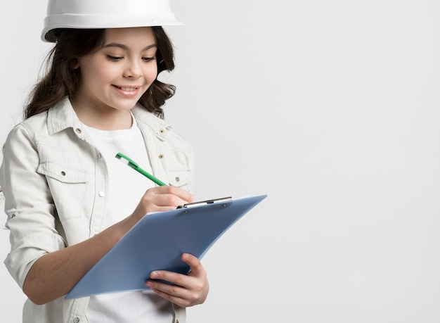 Front view young girl holding clipboard