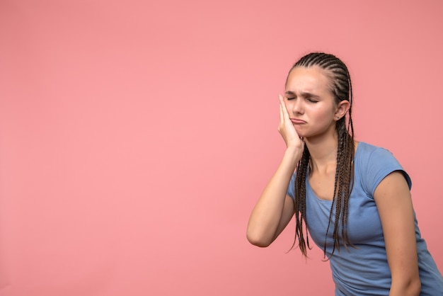 Front view of young girl hurt her toothache on pink