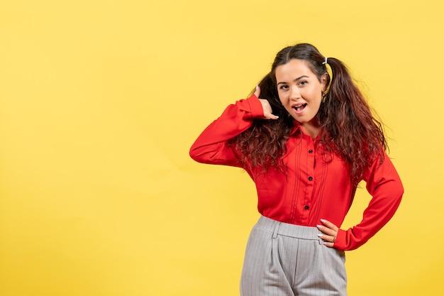 Вид спереди молодая девушка в красной блузке с милыми волосами, просто стоящая на желтом фоне, детский цвет, девочка, молодежь, невинность