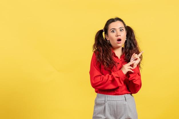 黄色の背景にショックを受けた顔を持つ赤いブラウスの正面図若い女の子無邪気な子供の女の子青年色の子供