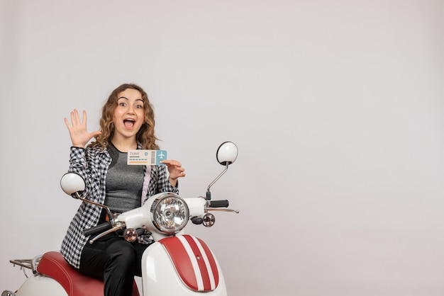 Vista frontale della giovane ragazza sul ciclomotore tenendo il biglietto agitando la mano sul muro grigio Foto Gratuite