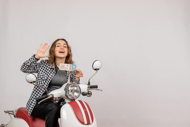 Vista frontale ragazza sul motorino che tiene il biglietto agitando la mano