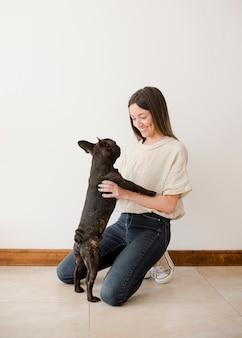 Вид спереди молодая девушка играет со своим щенком