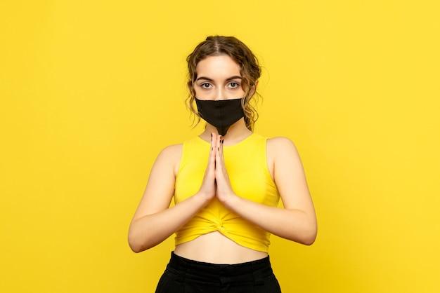 Vista frontale della ragazza che prega sulla parete gialla