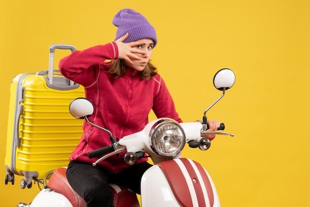 Giovane ragazza di vista frontale in cappello viola sul ciclomotore con la valigia