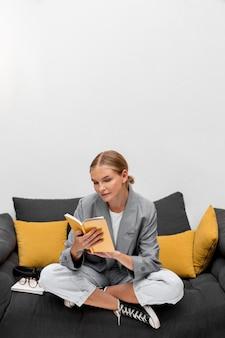 Вид спереди молодая девушка, читающая книгу