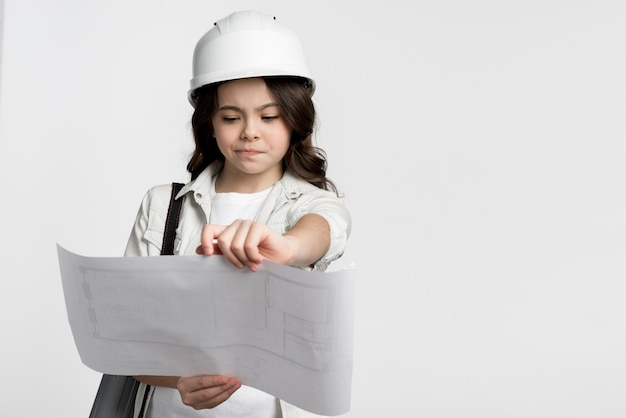 Front view young girl reading construction plan