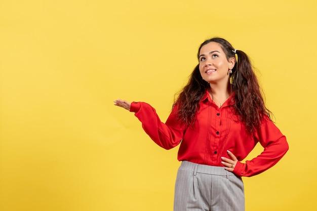 Vista frontale ragazza in camicetta rossa con capelli carini in posa su sfondo giallo bambino ragazza gioventù innocenza colori kid