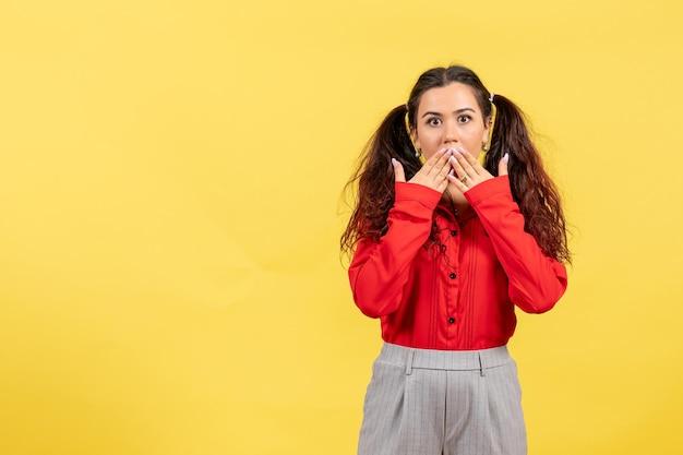 Vista frontale ragazza in camicetta rossa con capelli carini e viso scioccato su sfondo giallo bambino ragazzo ragazza gioventù colore innocenza