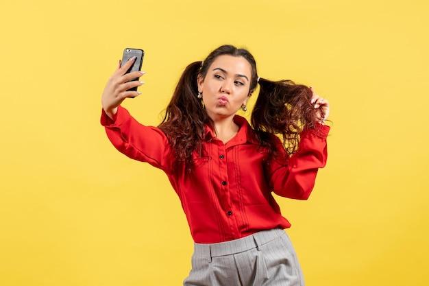 Vista frontale ragazza in camicetta rossa con capelli carini che si fanno selfie su sfondo giallo ragazzino ragazza gioventù innocenza colori bambino