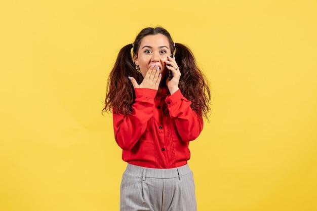 Vista frontale ragazza in camicetta rossa con capelli carini parlando al telefono su sfondo giallo bambino ragazza gioventù innocenza colore bambino
