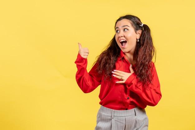 Vista frontale ragazza in camicetta rossa con espressione eccitata su sfondo giallo chiaro sentimento femminile bambino bambina ragazza emozione giovanile