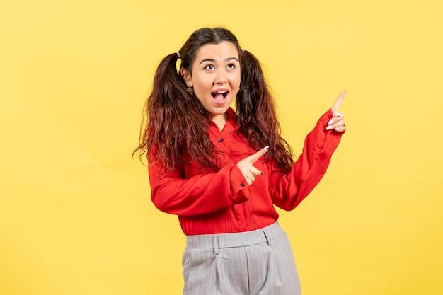 Vista frontale ragazza in camicetta rossa con espressione eccitata su uno sfondo giallo bambina bambina bambina ragazza sentimento emozione giovanile