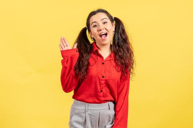 Vista frontale ragazza in camicetta rossa con espressione eccitata su sfondo giallo sentimento femminile bambino bambina ragazza emozione giovanile